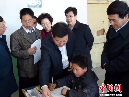 石家庄市委书记孙瑞彬(中)一行到赞皇县黄北坪小学看望贫困学生,调研山区扶贫攻坚。(资料图片)