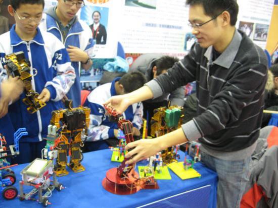 中关村中学辅导老师杨森林和同学展示自己设计的机器人和机器手